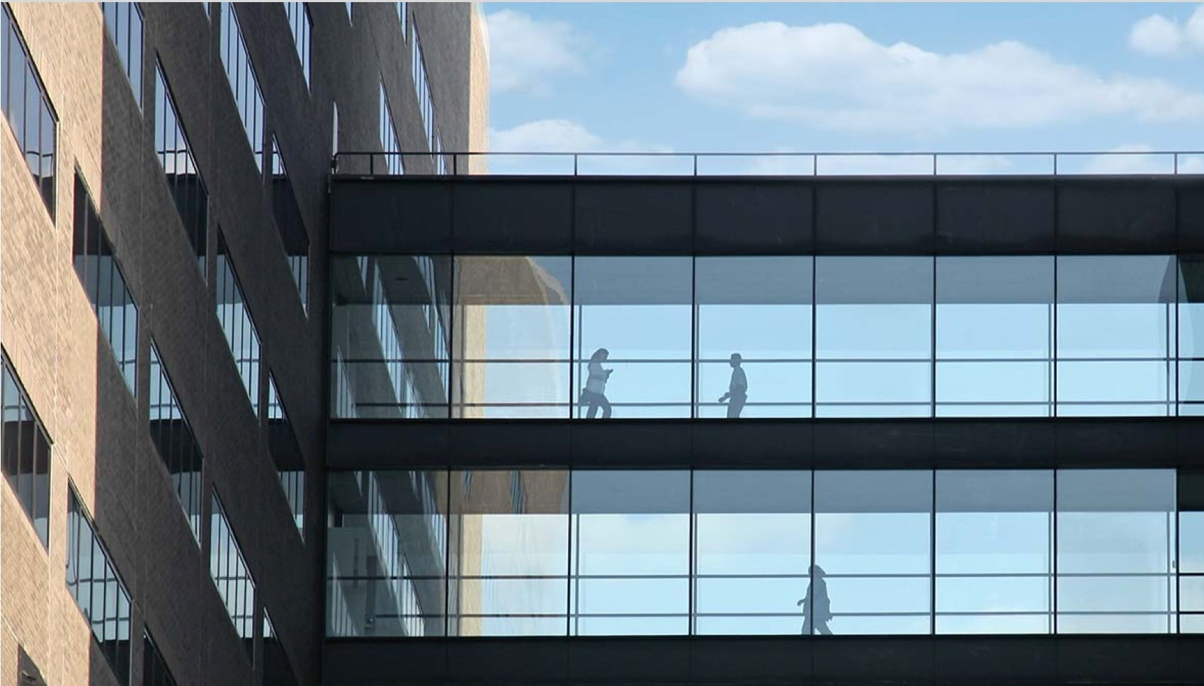 People are in a glass walkway between two modern building