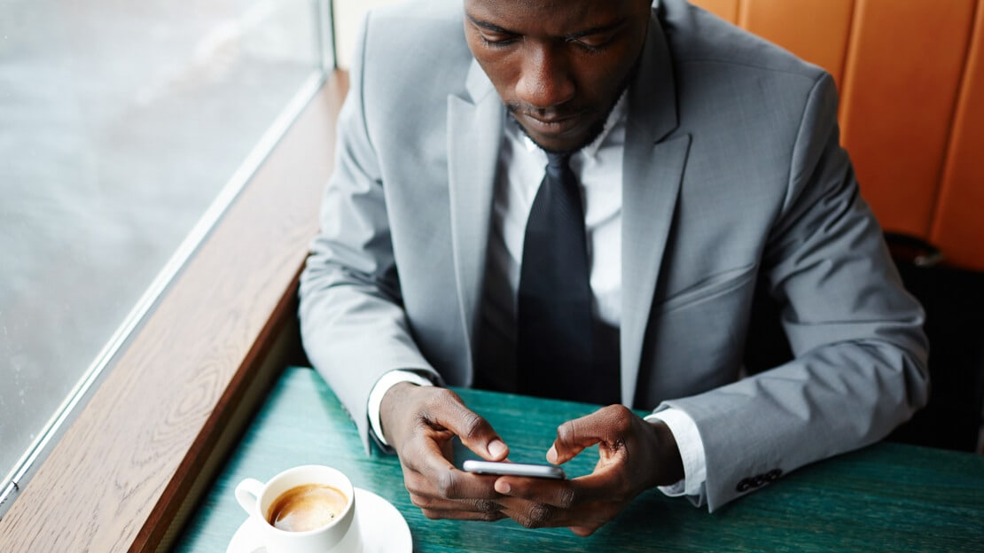 A businessman in a suit is sitting at a table with a cup of coffee, working on his mobile phone