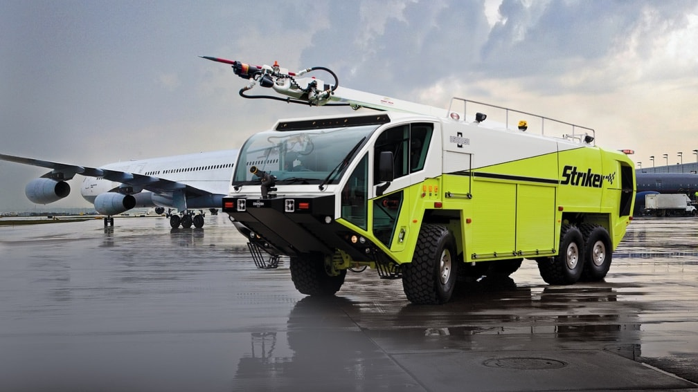 An airport maintenance vehicle is parked in front of a passenger jet on a tarmac