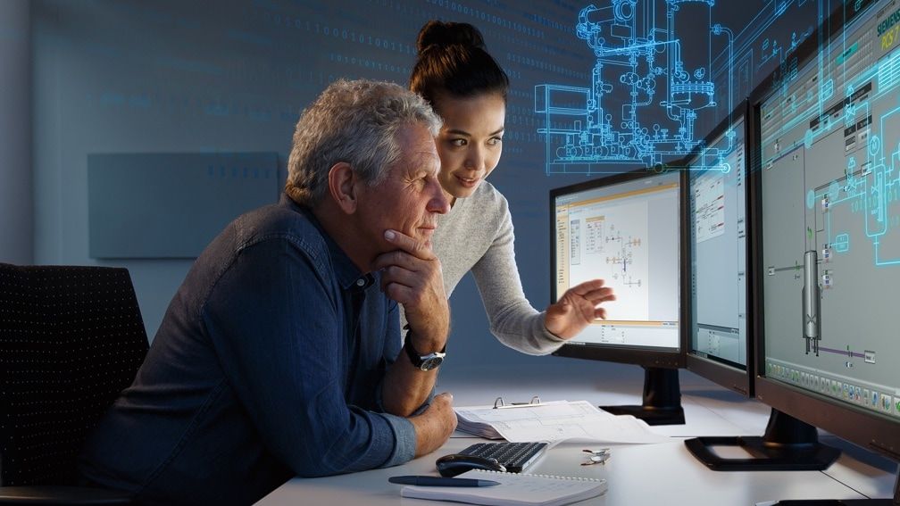 An older man and a younger woman at a desk looking at 3 PC monitors